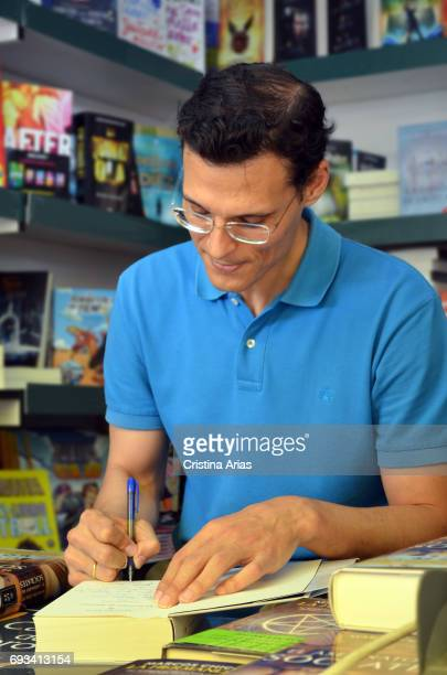 The writer Marcos Chicot signs a book during the Book Fair 2017 at El Retiro Park on June 3 2017 in Madrid Spain