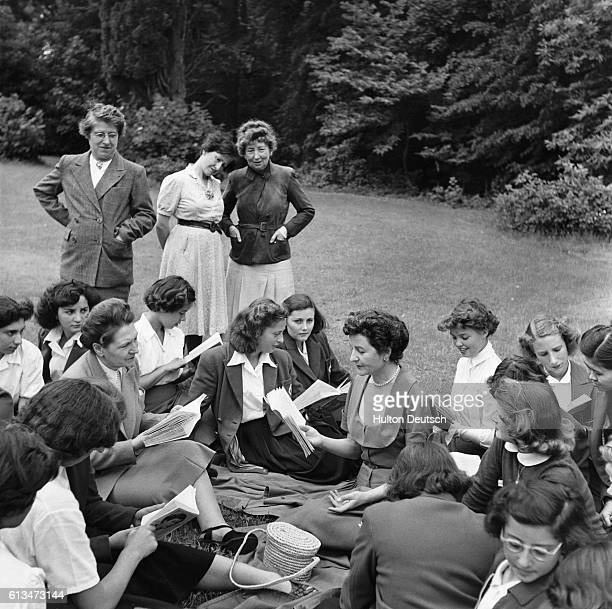 The writer Nancy Mitford, sits with some of the students from the College Feminin de Bouffemont finishing school and discusses her book.