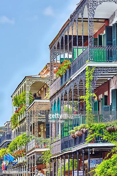 the wrought iron lace of a french quarter balcony - new orleans stock pictures, royalty-free photos & images