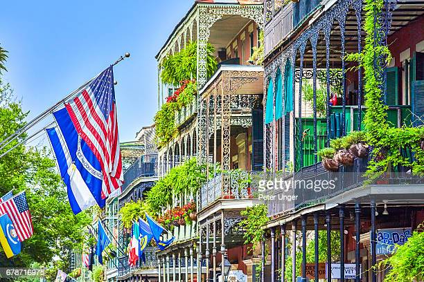 the wrought iron lace of a french quarter balcony - new orleans french quarter stock photos and pictures