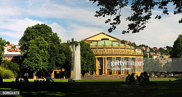 The Württemberg State Theatres, Opera, Ballet and Theatre. In the foreground people are sitting in the grass in the shadow of the trees and water...
