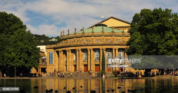 The Württemberg State Theatres with tourists and citizen and Eckensee with silhouettes of ducks in front Stuttgart Germany