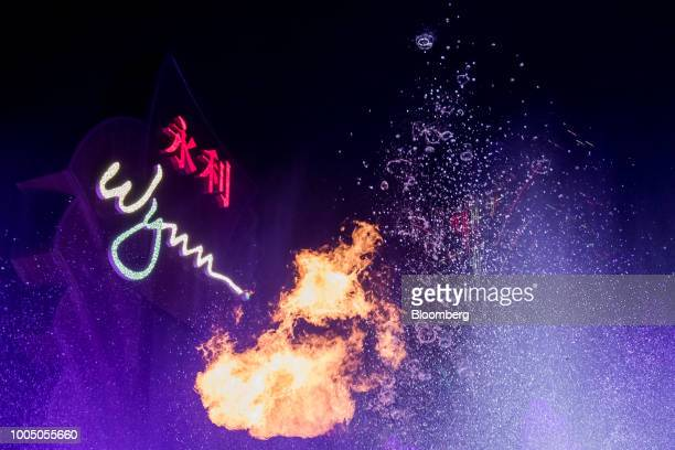The Wynn Resorts Ltd logo stands illuminated behind flames and sprays of water from the fountain show at the Wynn Macau casino resort in Macau China...