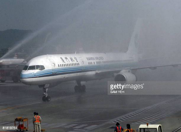 The Xiaman Airline plane carrying the first group of Chinese tourists to arrive in Taipei from Xiamen goes through a welcome water fountain provided...