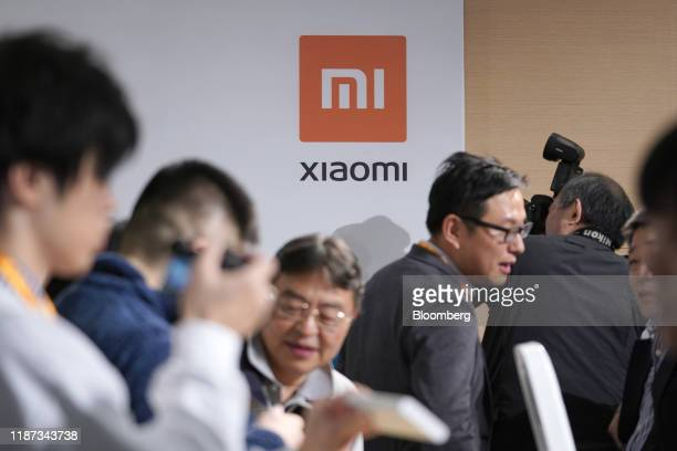 The Xiaomi Corp. Logo is displayed as attendees look at the company's Mi Note 10 smartphones during a news conference in Tokyo, Japan, on Monday,...