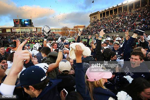 The Yale Bulldogs celebrate as students rush the field after their victory over the Harvard Crimson at Harvard Stadium on November 19, 2016 in...