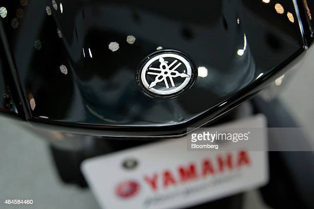 The Yamaha Motor Co logo sits on a Tricity threewheeled scooter with Leaning Multi Wheel mechanism on display at the company's showroom in Iwata...