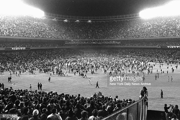 The Yankee Stadium infield is a sea of jubilant fans who stormed playing area after the New York Yankees' first championship since 1962 The Yankees...
