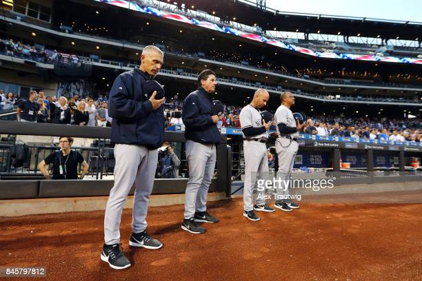 The Yankees coaching staff stands outside the dugout during the singing of the national anthem prior to the game between the New York Yankees and the...