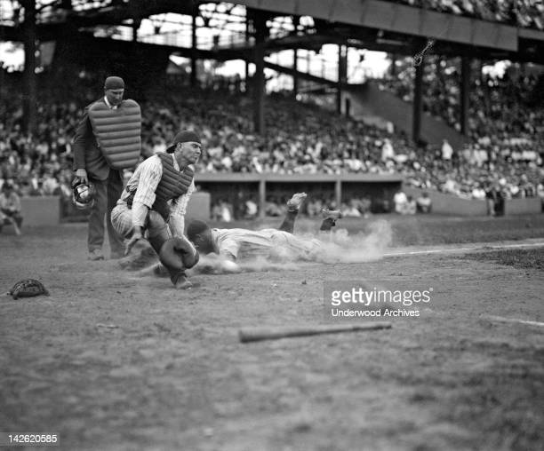 The Yankees Lou Gehrig scores head first in the fourth inning as Joe Harris's throw gets away from catcher Hank Severeid of the Washington Senators,...
