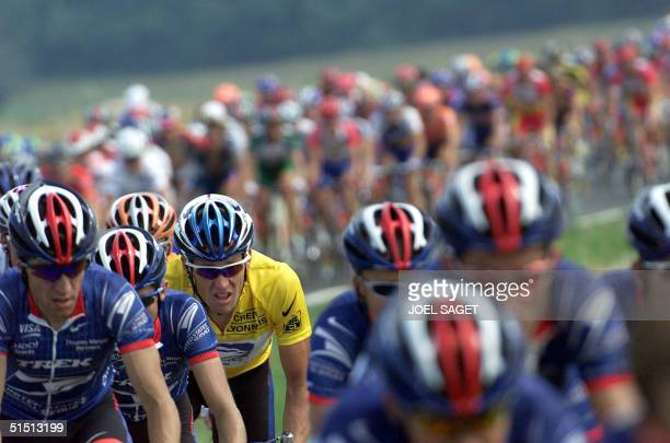 The yellow jersey, leader of the US Postal team, US Lance Armstrong rides among his teammates in the pack during the 19th stage of the 88th Tour de...
