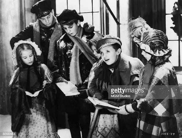 The young actor Terry Kilburn portraying Tiny Tim leans on his crutch and sings carols with other children in a still from the film A Christmas Carol