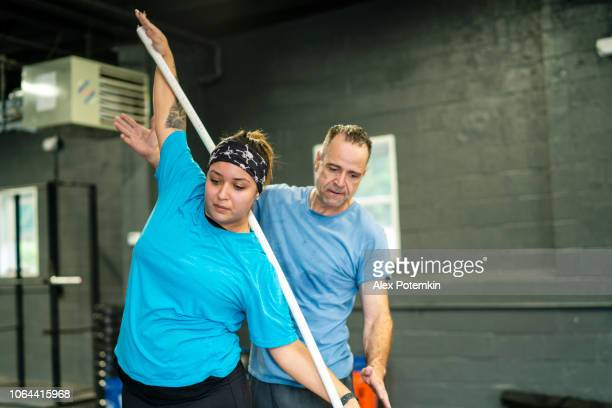 the young, beautiful cheerful body-positive latino woman doing stretching exercise with a pole under the supervision of the senior latinx man, the coach, in the gym - alex potemkin or krakozawr latino fitness stock photos and pictures