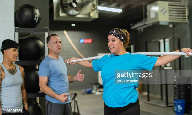The young, beautiful cheerful body-positive Latino woman doing stretching exercise with a pole under the supervision of the Senior Latinx man, the coach, in the gym