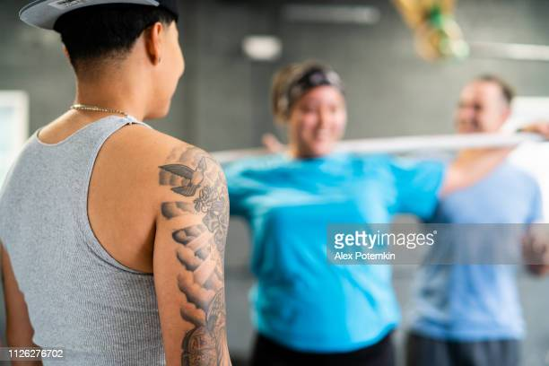 The young, beautiful cheerful Latino woman with the tattoo looking how her girlfriend doing stretching exercise in the gym