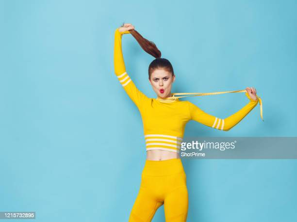 the young beautiful woman of a sports constitution in a sports suit smothers herself with a centimeter because she is not thin enough. - world sports championship stock pictures, royalty-free photos & images