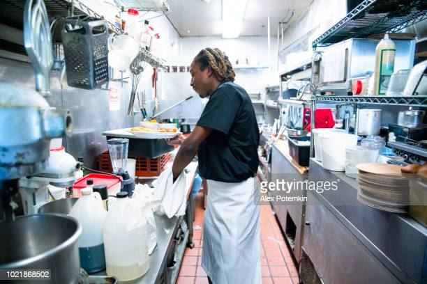 The young Black man working on the industrial kitchen