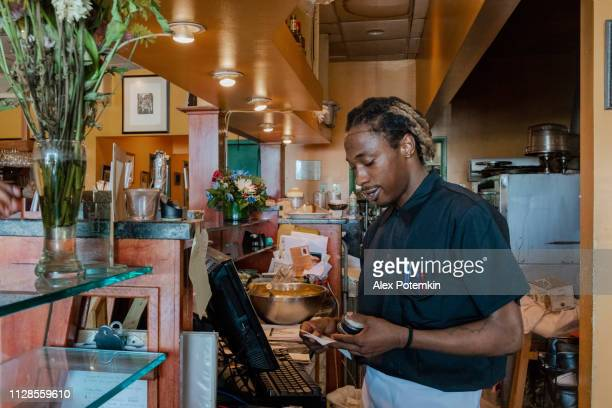 The young Black man working with the cash register behind the counter of the small local restaurant