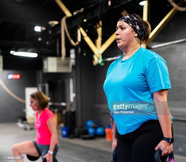 las jóvenes positivas para el cuerpo, y las mujeres latinas de 55 años haciendo intensificar con el ejercicio de peso en el gimnasio - 50-59 years and women only fotografías e imágenes de stock