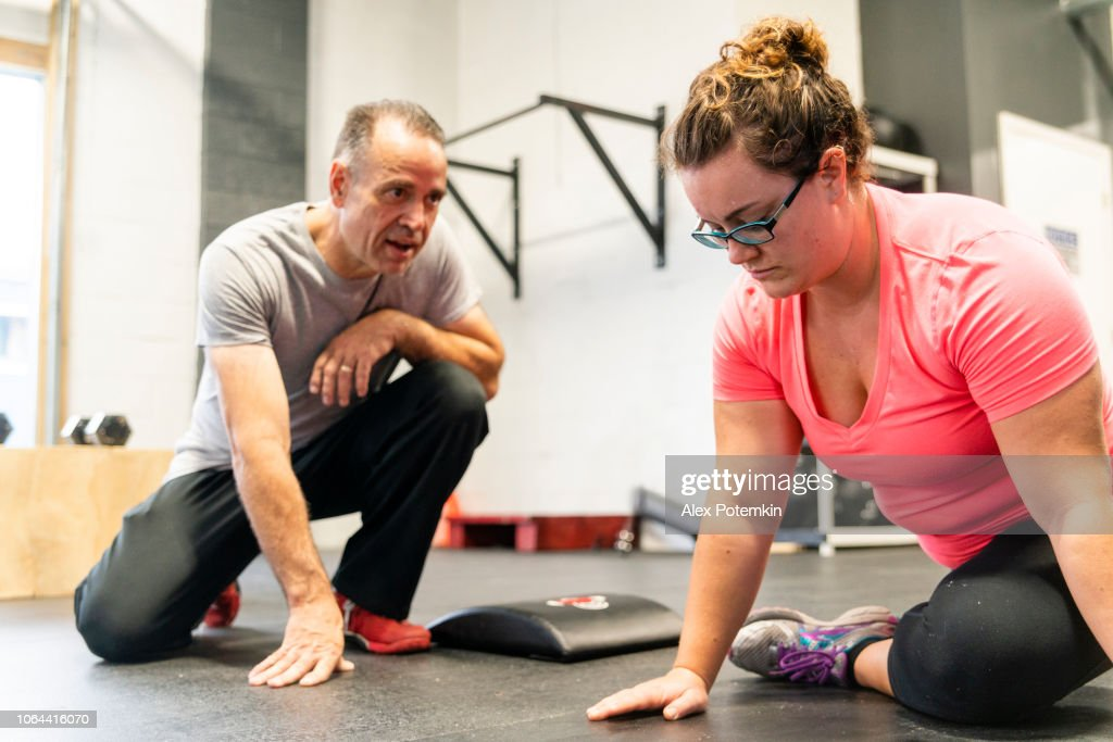 The young, body-positive Caucasian woman doing stretching workout under the supervision of the Senior, 55-years-old, male Latino coach. : Stock Photo