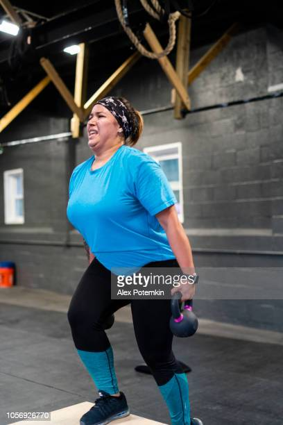 the young, body-positive latino woman doing step-up with weight exercise in the gym - alex potemkin or krakozawr latino fitness stock photos and pictures