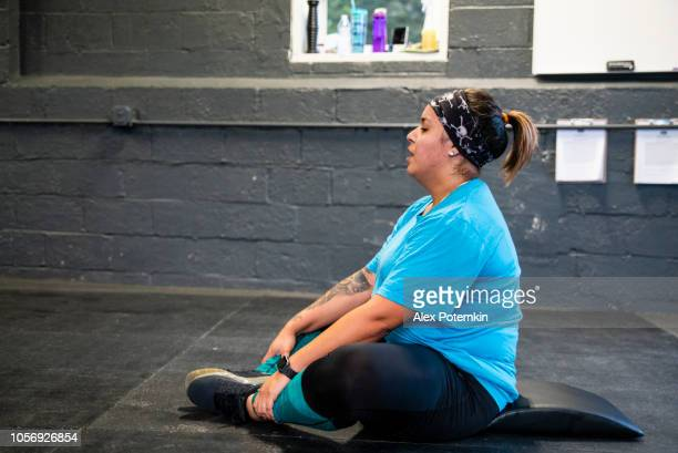 the young, body-positive latino woman doing stretching exercise in the gym - alex potemkin or krakozawr latino fitness stock photos and pictures