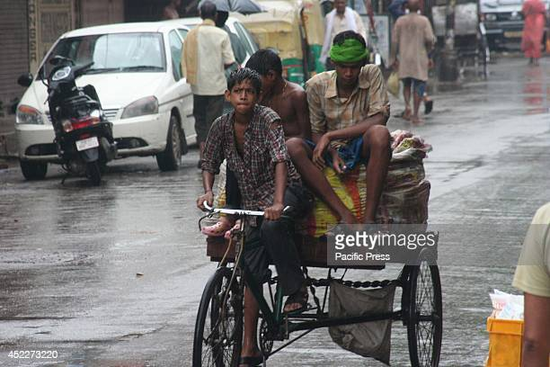 The young boys ride a cycle trolley in a rainy morning going to work in Varanasi Many parts of North India received light to heavy rainfall as part...