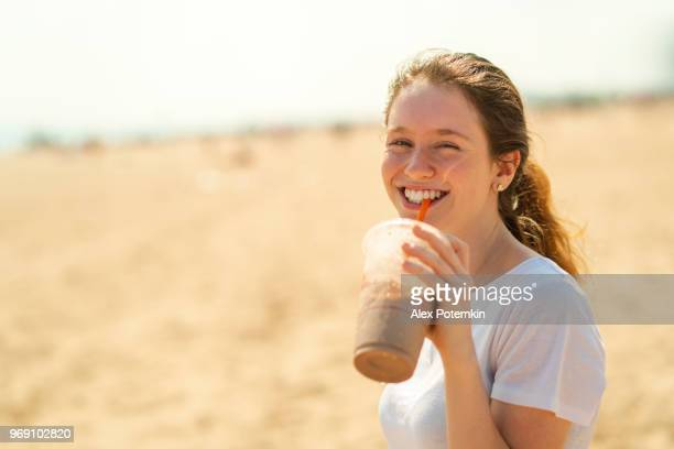 the young cheerful 18-years-old girl drinking a milkshake on brighton beach - 18 19 years stock pictures, royalty-free photos & images