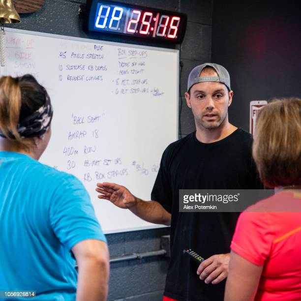 the young coach explaining the plan of a workout to the group of the latino women - alex potemkin or krakozawr latino fitness stock photos and pictures