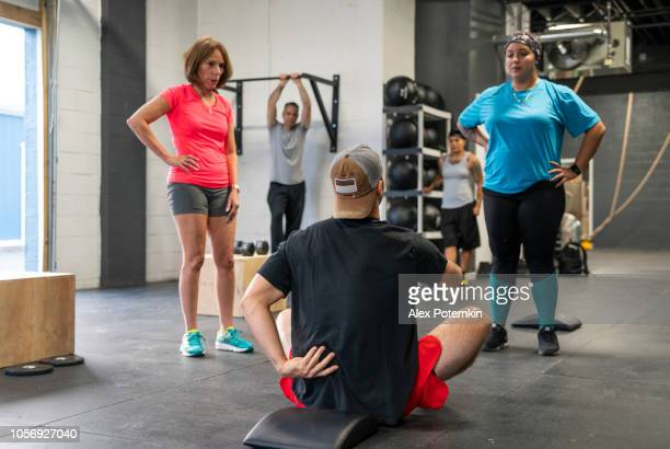 the young coach showing how to properly execute exercise to the group of the latino women - alex potemkin or krakozawr latino fitness stock photos and pictures