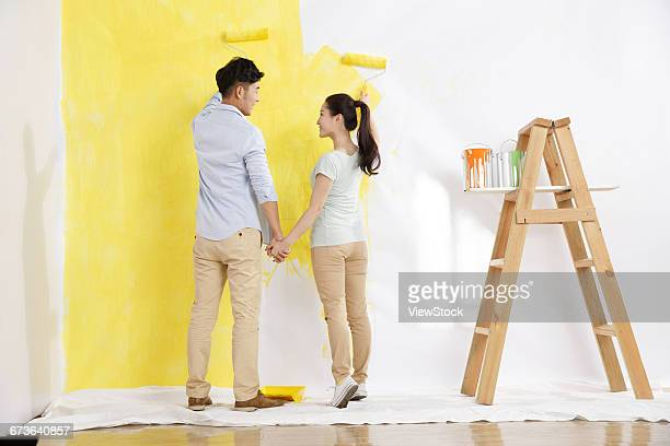The young couple were painting the walls