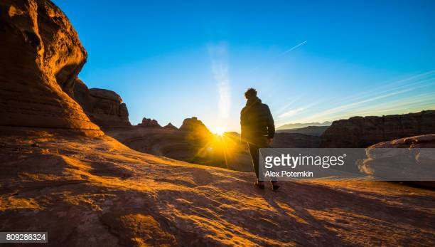 the young hipster man, traveler and hiker, admiring the sunrise in the red canyon near by delicate arch, utah, at sunrise - utah stock pictures, royalty-free photos & images