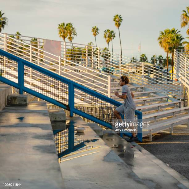 the young hispanic athlete doing steps running on the outdoor public stadium - alex potemkin or krakozawr latino fitness stock photos and pictures