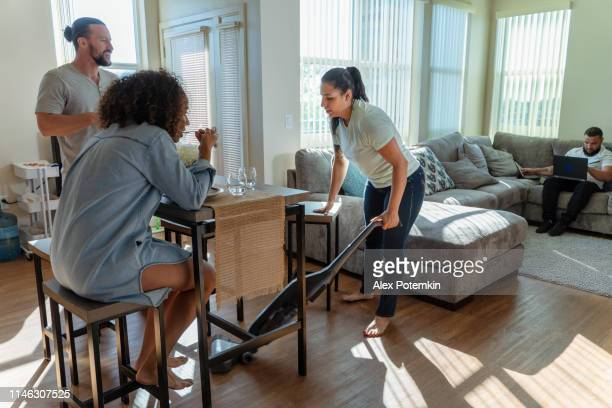 the young hispanic/latino woman cleaning the shared apartment with a vacuum cleaner, when her friends - roommates have some food in the kitchen, and another roommate working in on a couch in a living room with pc laptop. - sharing economy stock pictures, royalty-free photos & images