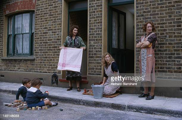 The young Kray twins play in the street as their mother Violet scrubs the front step of their east end home, in a scene from 'The Krays', directed by...