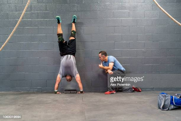 the young latino athlete doing armstand exercise, emotionally pushing by his coach, the senior 55-years-old latinx man. - alex potemkin or krakozawr latino fitness stock photos and pictures