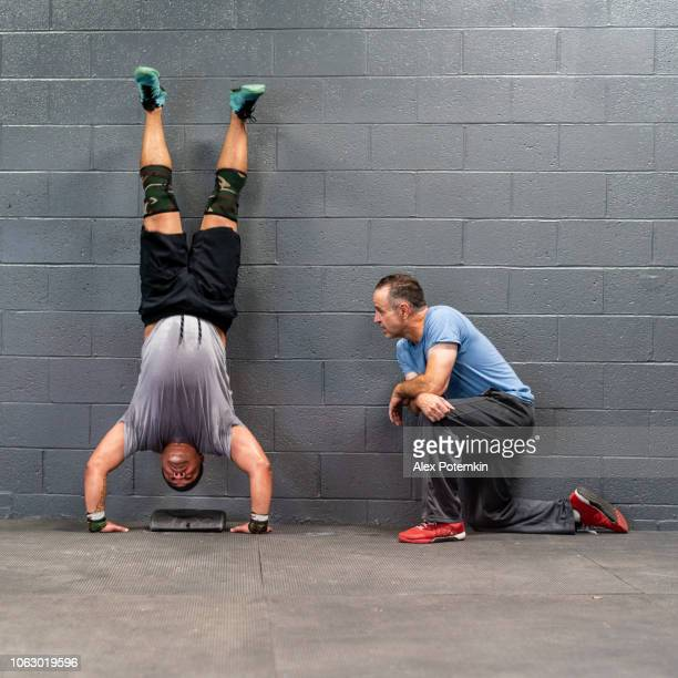 the young latino athlete doing armstand exercise, emotionally pushing by his coach, the senior 55-years-old latinx man. - 55 59 years stock pictures, royalty-free photos & images