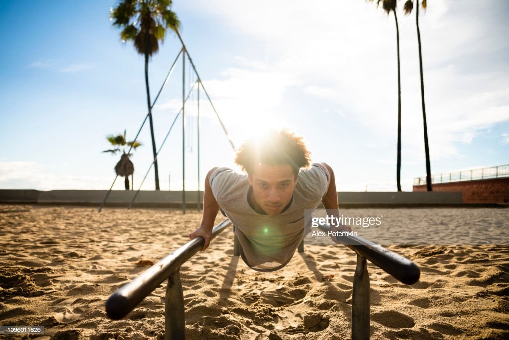 The young Latino man doing push-up exercise on the bars : Stock Photo
