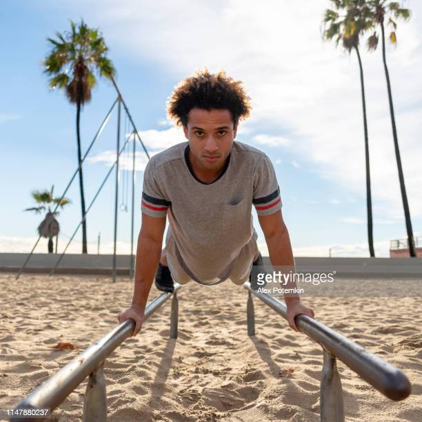 the young latino man doing push-up exercise on the bars - alex potemkin or krakozawr latino fitness stock photos and pictures