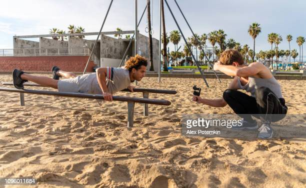 the young latino man doing push-up exercise on the bars when his friend filming it with the action camera - alex potemkin or krakozawr latino fitness stock photos and pictures