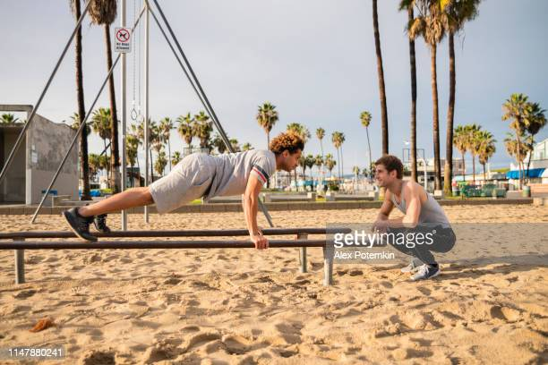 the young latino man doing push-up exercise on the bars, when his caucasian-white friend supporting him. - alex potemkin or krakozawr latino fitness stock photos and pictures