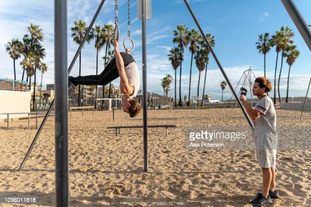 the young latino man filming his friend's gymnastic workout with the action camera - alex potemkin or krakozawr latino fitness stock photos and pictures