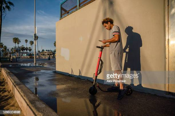 the young latino man uses his smartphone to book electrical scooter at venice beach, california, usa - alex potemkin or krakozawr latino fitness stock photos and pictures