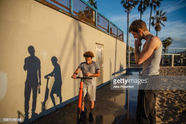 The young Latino man uses his smartphone to book electrical scooter at Venice Beach, California, USA