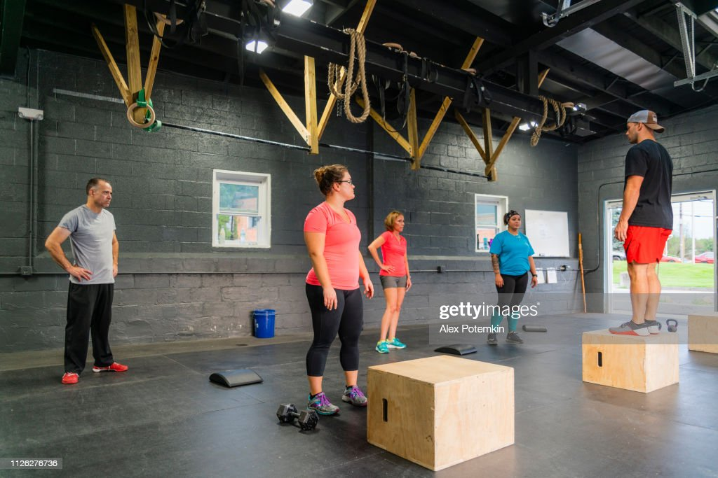 The young male coach demonstrating how to do step-ups on the cube to the group of women in the gym : Stock Photo