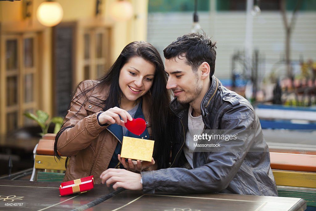 The young man gives a gift to  girl : Stock Photo
