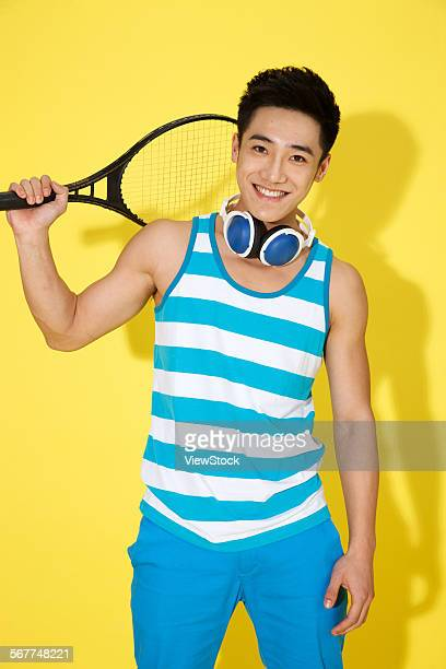 The young man holding a tennis racket