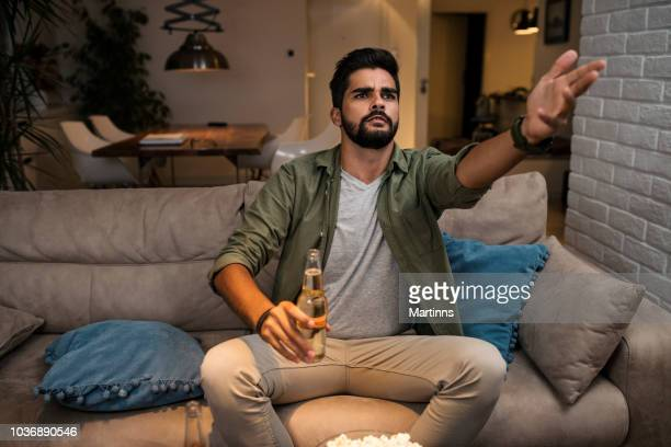 the young man is watching a sports game on tv - fan enthusiast stock pictures, royalty-free photos & images