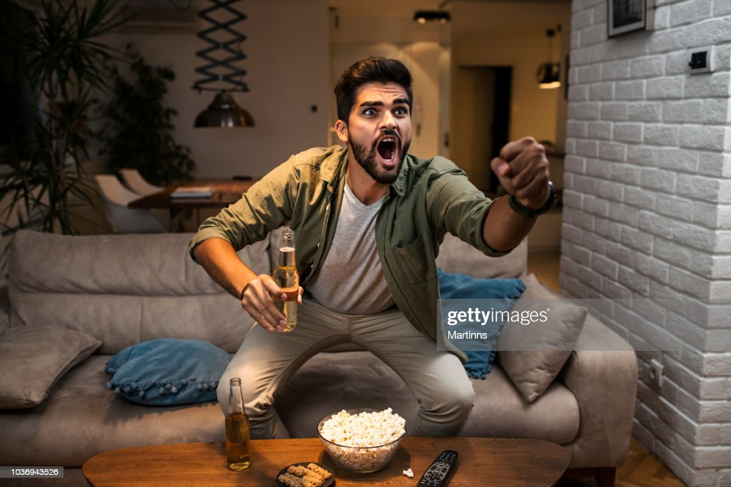 The young man is watching a sports game on TV : Stock Photo