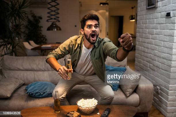 the young man is watching a sports game on tv - futebol imagens e fotografias de stock